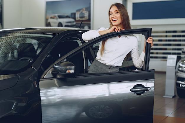 喜びで彼女の新しい車に触れる美しい若い女性