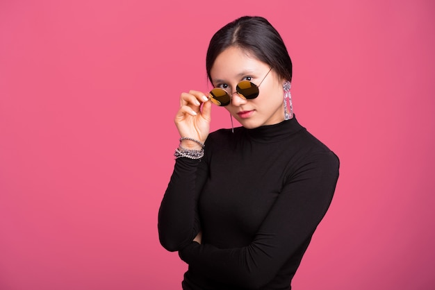 Beautiful young woman touching sunglasses and looking at the camera