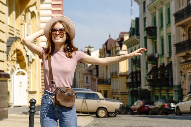 Beautiful young woman tourist pleasant walk in the city center catching taxi.