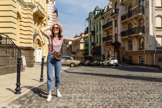美しい若い女性観光客がタクシーを引く市内中心部で快適な散歩。