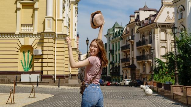 Красивый турист молодой женщины приятная прогулка в центре города.