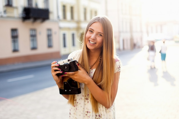 Beautiful young woman tourist poring on the street in summer with camera