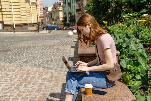 Красивая молодая женщина турист с вынос кофе в центре города, используя ноутбук.