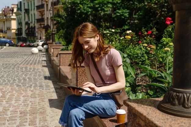 Красивый турист молодой женщины с takeout кофе в центре города используя пк таблетки.