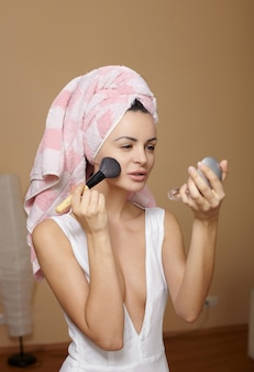 Beautiful young woman in towel on the head applying makeup in the mirror