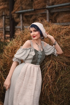 Beautiful young woman in a traditional bavarian costume is standing near the haystacks on the farm