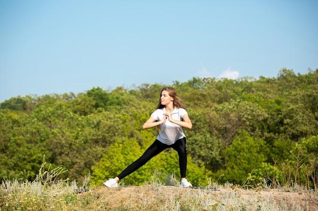 Красивая молодая женщина тренирует гибкость на открытом воздухе