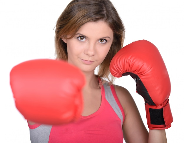 Beautiful young woman training and wearing boxing gloves