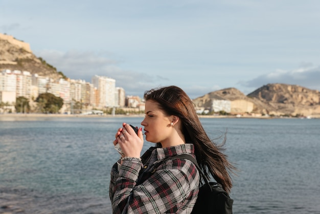 美しい若い女性旅行者は屋外の海を見下ろすコーヒーを飲みます