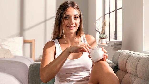 Bella giovane donna che prova i prodotti di bellezza