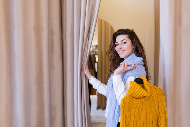 Beautiful young woman trying on clothes bought in a fitting shop