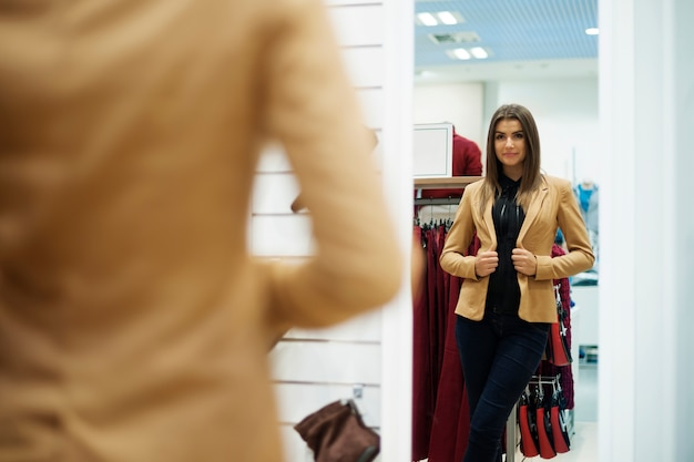 Beautiful young woman trying on jacket in front of mirror