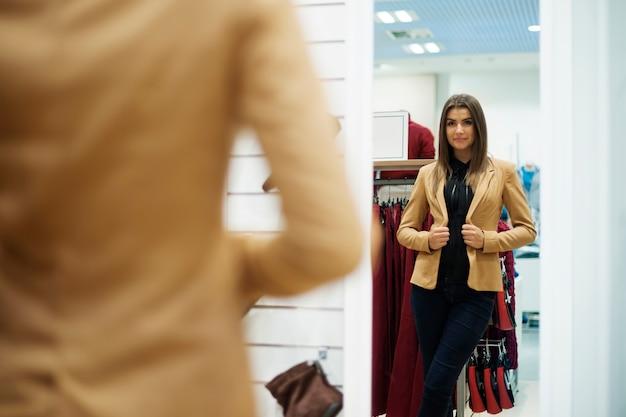 Bella giovane donna che prova sulla giacca davanti allo specchio