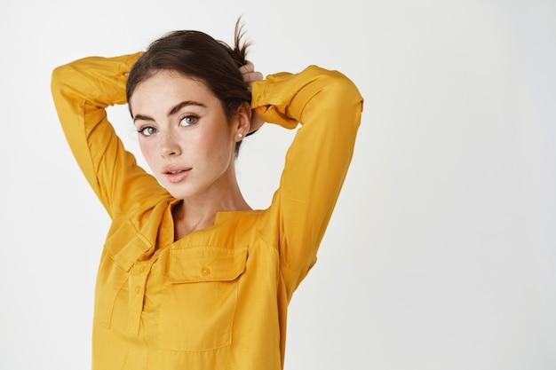 Красивая молодая женщина связывает волосы в пучке и смотрит в камеру, стоя над белой стеной