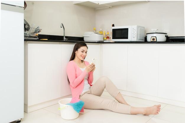 모바일로 타이핑을 하는 아름다운 젊은 여성, 청소할 물건이 있는 양동이 근처 집 바닥에 앉아