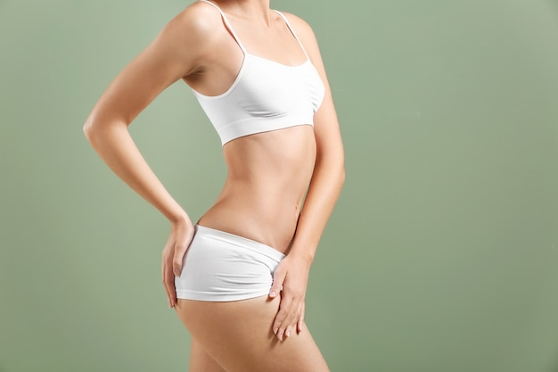 Beautiful young woman in underwear on green. plastic surgery concept
