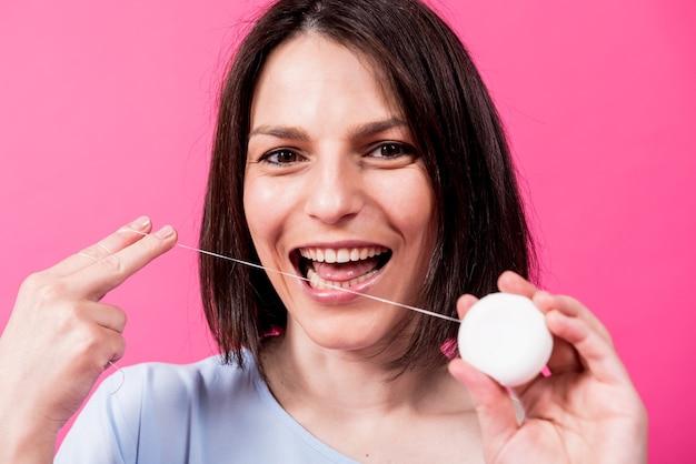 Красивая молодая женщина использует зубную нить на розовом фоне