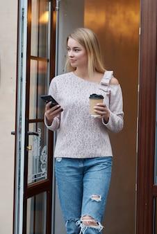 美しい若い女性は、スマートフォンのアプリケーションを使用してテキストメッセージを送信します。