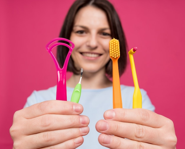 Beautiful young woman uses an oral care kit consisting of a tongue scraper single tufted and interde...