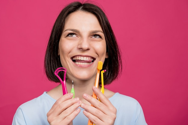 Beautiful young woman uses an oral care kit consisting of a tongue scraper single tufted and interdental brush