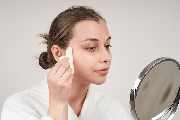Beautiful young woman uses quartz stone to massage her face while looking in the mirror