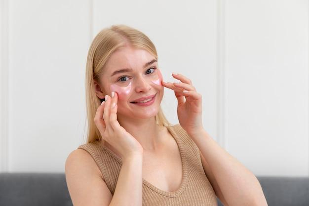 얼굴 관리 제품을 사용하는 아름다운 젊은 여성