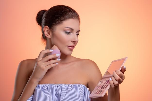 Beautiful young woman using beauty sponge for applying foundation
