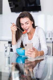 Красивая молодая женщина используя сотовый телефон пока делающ салат в кухне. здоровая пища. овощной салат. рацион питания. здоровый образ жизни. готовим дома.