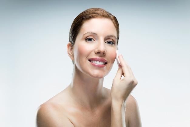 흰색 배경 위에 화장품을 사용하는 아름 다운 젊은 여자.