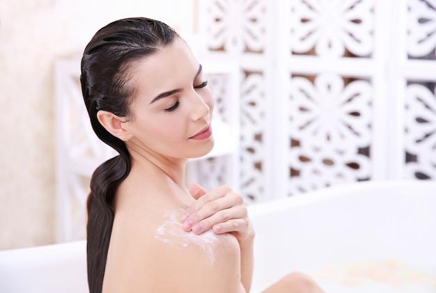 自宅で入浴しながら化粧品を使用して美しい若い女性