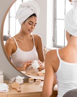 Красивая молодая женщина, используя дневной крем дома