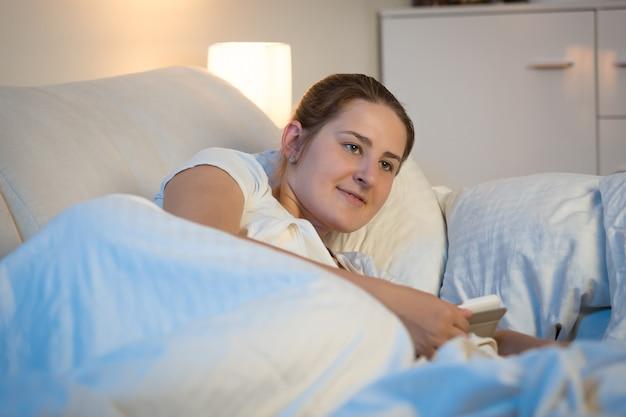夜のベッドでデジタルタブレットを使用して美しい若い女性