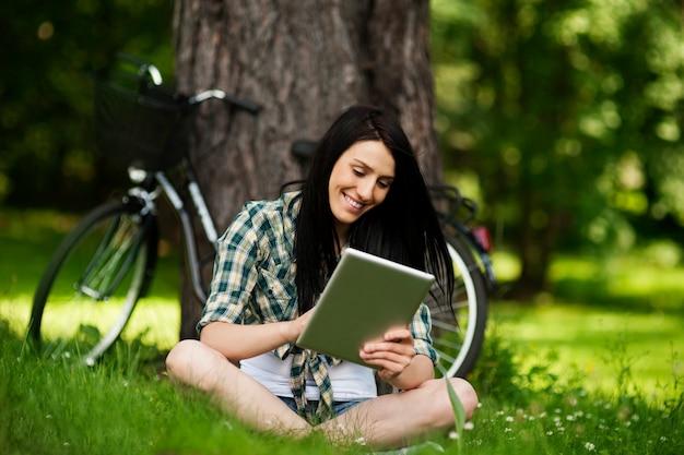 屋外でデジタルタブレットを使用して美しい若い女性