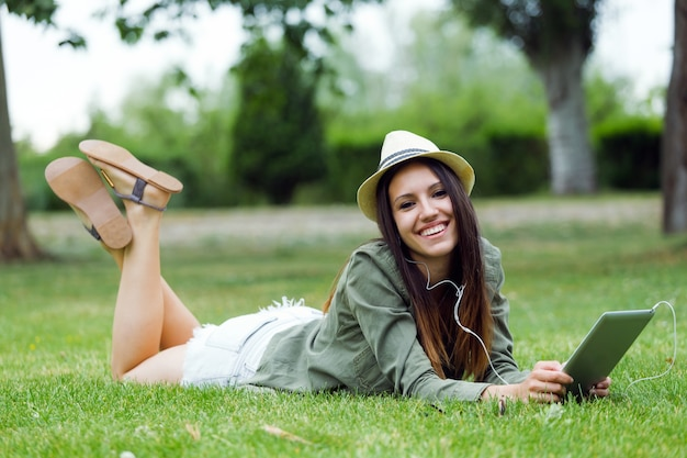 Beautiful young woman using digital tablet in the park.