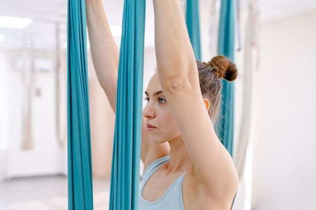 Beautiful young woman using hammock for yoga
