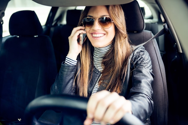 Beautiful young woman using her mobile phone in the car.