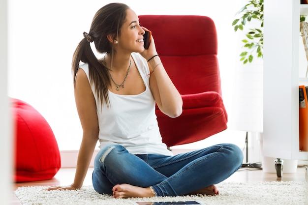 Bella giovane donna che utilizza il suo cellulare in casa.