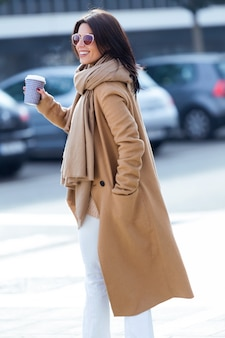 Красивая молодая женщина, используя ее мобильный телефон на улице.