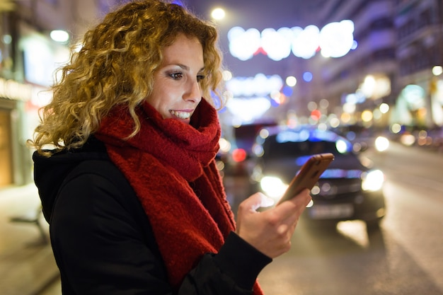 Beautiful young woman using her mobile phone in the street at night.