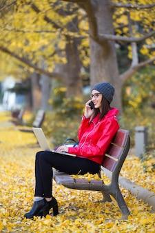 가 노트북을 사용하는 동안 그녀의 휴대 전화를 사용 하여 아름 다운 젊은 여자.