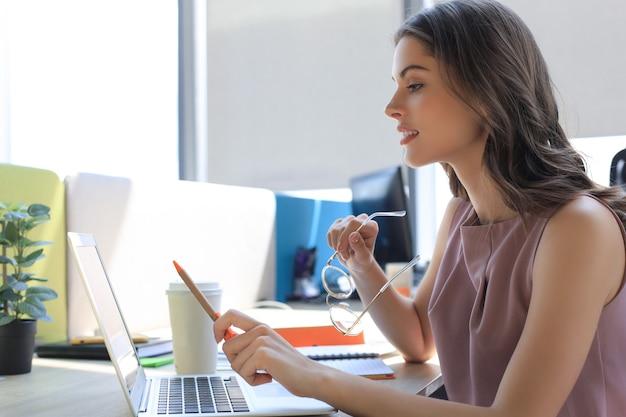 ラップトップを使用して、彼女の職場に座ってそれを見ている美しい若い女性。