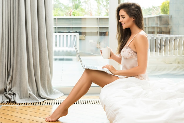 Beautiful young woman using laptop and drinking coffee