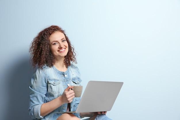 光の壁にラップトップを使用して美しい若い女性