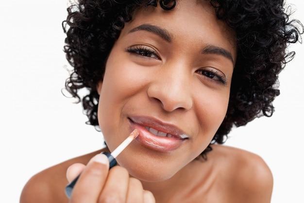 Beautiful young woman using lip brush while making-up