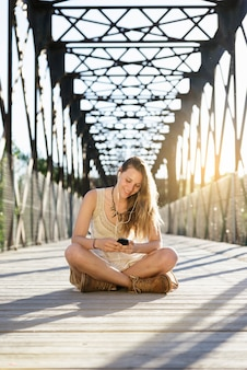 Beautiful young woman using mobile in the park.