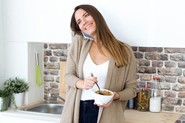 美しい若い女性が携帯電話を使用し、家庭で穀物を食べる。