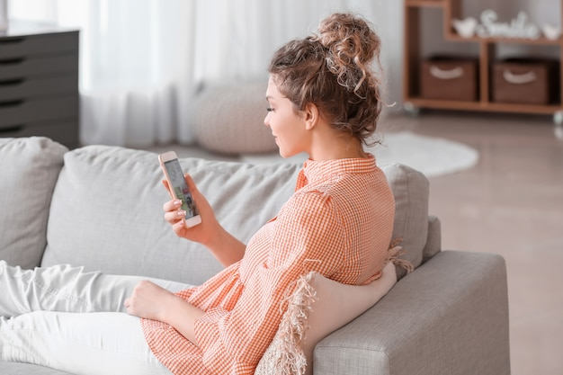 Beautiful young woman using mobile phone for online shopping at home