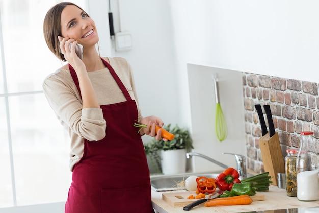 Bella giovane donna che utilizza telefono cellulare durante la cottura in cucina.