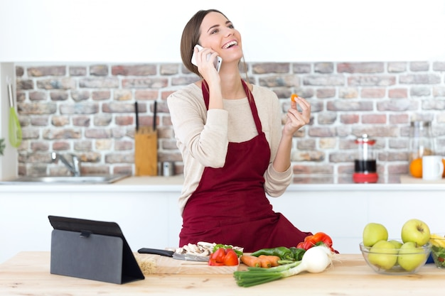 Beautiful young woman using mobile phone while cooking in the kitchen.