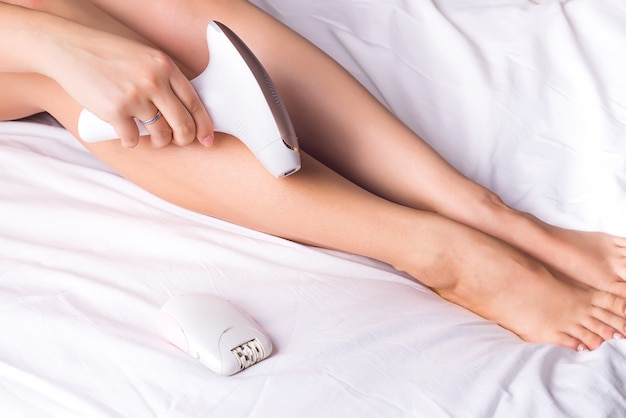 Beautiful young woman using a photo epilator for a hair and removing hair